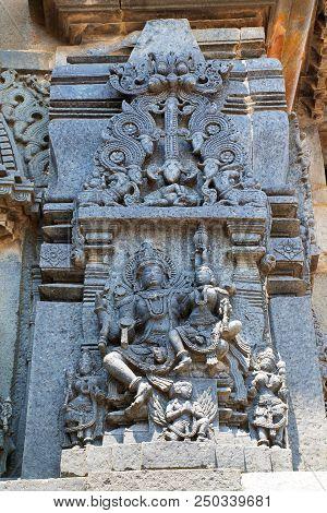 Ornate wall panel reliefs depicting Lord Vishnu with his consort Lakshmi sitting in his lap, Chennakesava temple, Belur, Karnataka, india. poster