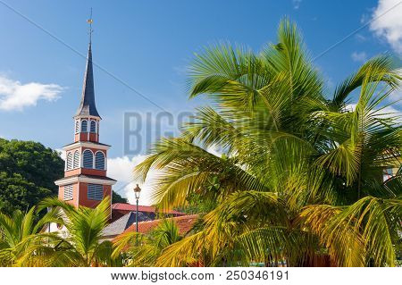 Petite Anse d'Arlet village, with Saint Henri Church and palm trees poster