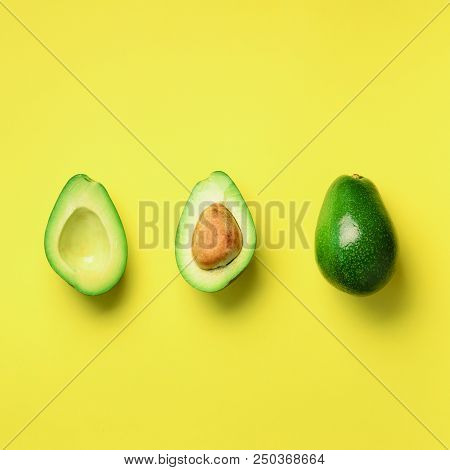 Organic Avocado With Seed, Avocado Halves And Whole Fruits On Yellow Background. Top View. Square Cr