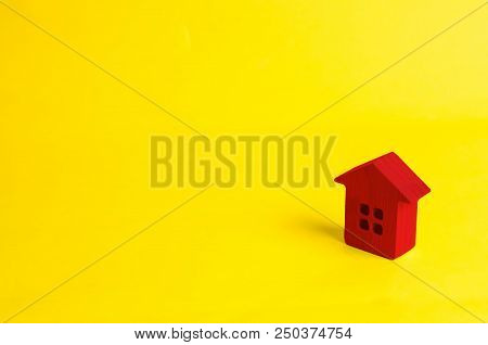 A Small Red Wooden House Stands On A Yellow Background. The Concept Of Buying And Selling Real Estat
