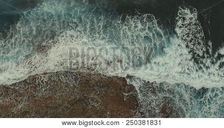 Aerial Photography. A Foamy Large Sea Wave Is Broken Against The Rocks.