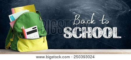 Back to school shopping baackpack. Accessories in student bag against chalkboard