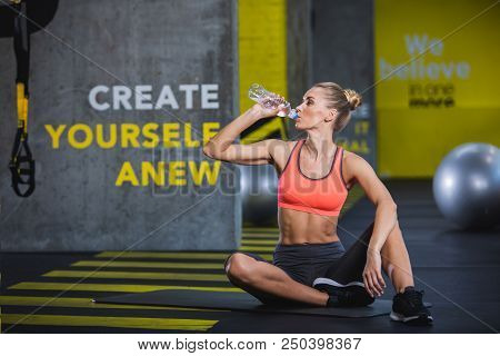Slim Woman Is Sitting On Mat In Fitness Center And Resting After Work Out. She Is Quenching Thirst W