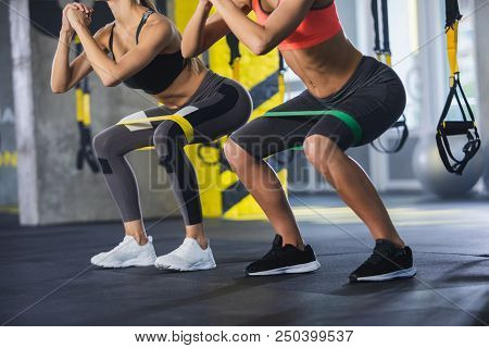 Close Up Of Athletic Women In Squat Together In Gym. Couple Of Fit Girls Are Exercising With Resista