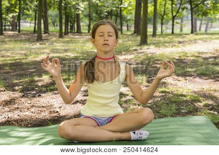 Girl's Happy And Meditate On The Practice Of Yoga In The Park , Yoga Kid. Healthy Lifestyle - Little