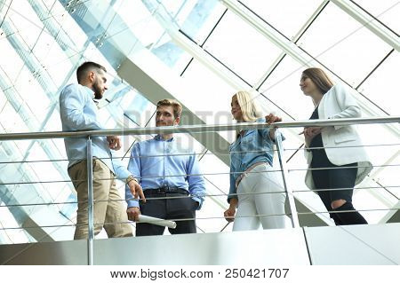 Bottom View. Modern People In Casual Wear Having A Brainstorm Meeting While Standing In The Creative