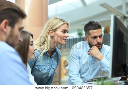 Group Of Young Modern People In Smart Casual Wear Having A Brainstorm Meeting While Standing In The