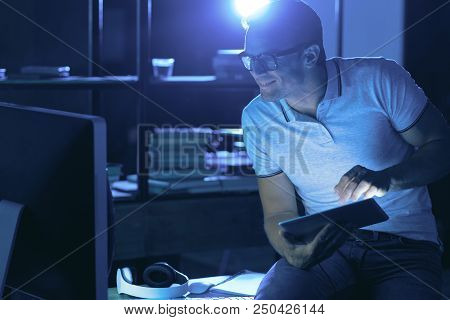 Professional Programmer. Pleasant Nice Handsome Man Holding A Tablet And Looking At The Computer Scr
