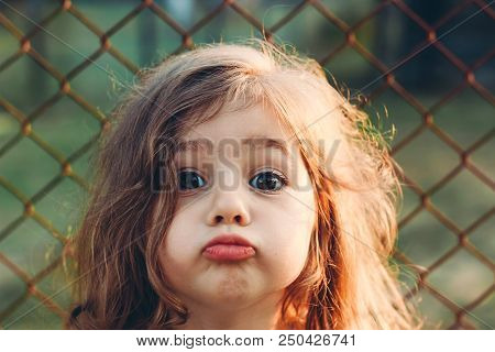 Portrait Of Cute Little Girl With Kissing Lips Looking At Camera. Happy Kid Outdoors