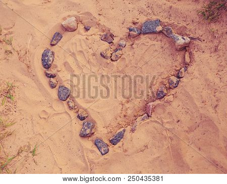 Drawing Heart Of Stones Laid On Warm Sand. Toned, Soft Focused