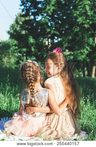 Toned Portrait Of Two Happy Little Girls Embracing  And Spending Time At Sunny Summer Park