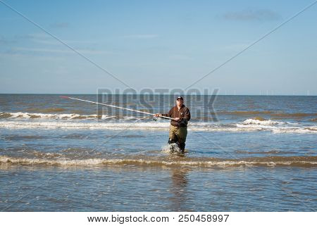 Egmond-aan-zee, Netherlands - 2016-04-10: Fisherman With Rod Walking Back To The Shore. Sea Fishing