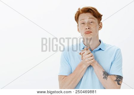 Please help me out my friend. Miserable funny european male coworker with red hair and freckles, clenching hands together over chest, pursing lips and whining, asking for favour or wanting something. Emotions concept poster