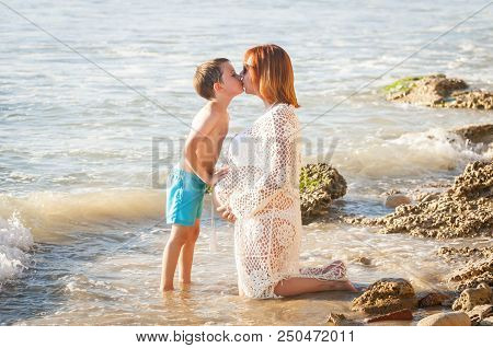 Cute Caucasian Child Kissing His Pregnant Mother And Touching Her Belly At The Seaside.