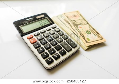 Calculator with US Dollars, Calculator and Money Banknote, Finance and Savings, American Dollar Banknotes, Calculator with Background of US Dollar Banknotes, United States Government Tax Calculation