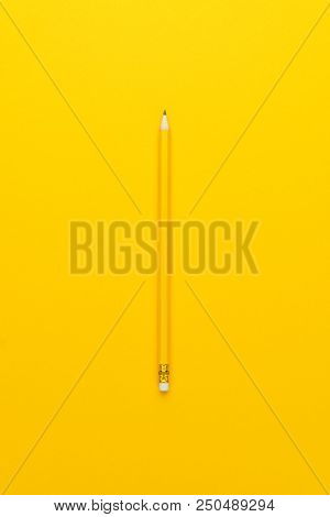 Yellow Pencil. Pencil With Eraser On Yellow Background. Minimalistic Image Of Yellow Pencil. Pencil