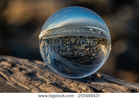 Cobblestone Shoreline Of The Beach Distorted By The Spherical Lens On Textured Driftwood.