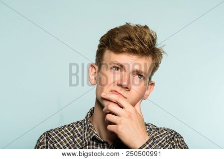 Puzzled Confused Man Scratching His Chin Thinking Of Smth Looking Up. Portrait Of A Young Guy On Lig