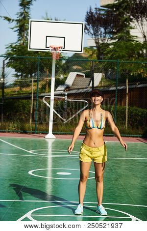 Beautiful Young Woman Playing Basketball Outdoors. The Girl Basketball Player Have Training And Exer