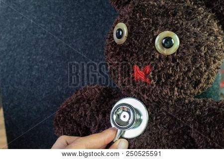 Doctor's Hand Holding Stethoscope Put On Cute Brown Handmade Fluffy Doll With Pitty Eyes, Healthcare