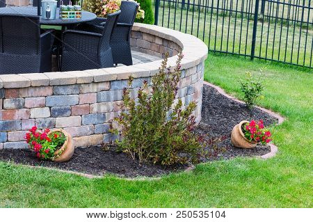 Curved Round Brick Wall On An Outdoor Patio With Feature Flowerbed In A Neat Green Lawn And Wicker A