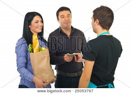 Couple Paying With Money At Supermarket