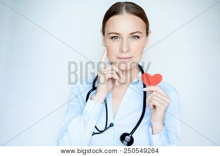 Portrait of a cardiologist doctor, serious woman wearing medical uniform with stethoscope holding in hand little red paper heart, like a symbol of the life
