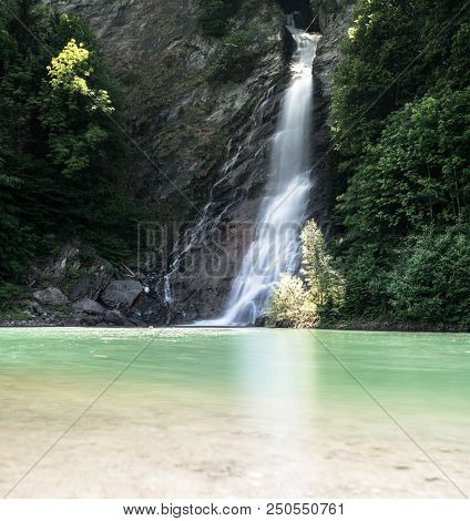 waterfall in midst of forest landscape cascading into a colorful turquoise and brown pond poster