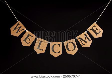 Welcome Home Banner. Greeting Letters Hanging On Bunting. Welcoming Text On String Against Black Bac