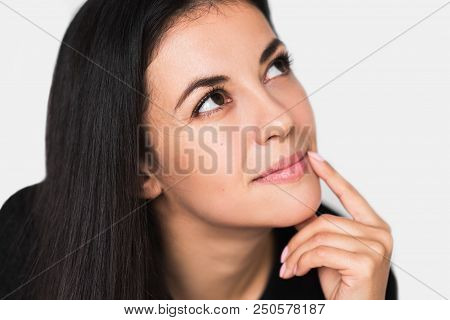 Close Up Portrait Of Brunette Cute Dreamy Woman With Hand On Lips. Young Pretty Woman Looking Up And