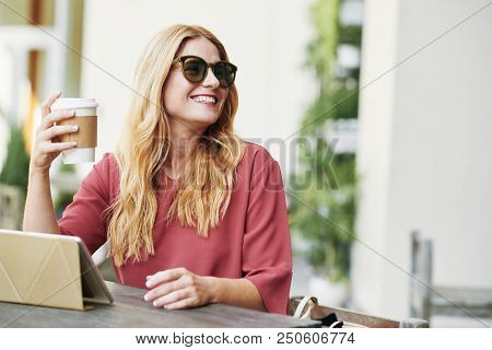 Happy Beautiful Young Woman In Sunglasses Drinking Coffee And Using Touchpad At Coffee Shop