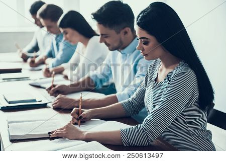 Young People Studying In Classroom At College. Education Concept. Writing On Lesson. Multiethnic Stu