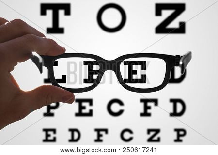 hands holding glasses in front of a vision test with blurry and sharp areas