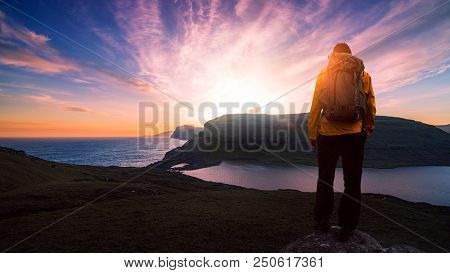 successful male backpacker hiking on mountain peak cliff with a beautiful sunset and sky