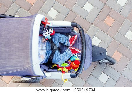 Baby Sleeping Three-wheel Stroller Outdoor. Child In Bright Casual Costume Lying At Big Comfortable