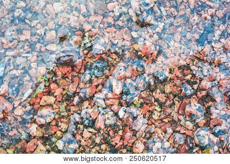 Brown texture of wet red granite Gravel. Sand and stones in water on the floor background. The ground is covered with stone fractions poster