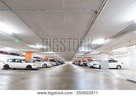 Underground Interior Garage Parking Lot With Many Cars.