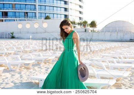Beautiful Woman In A Green Gown On The Beach