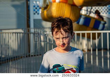 View Of Happy Young Boy Having Fun On Boardwalk Amusement Ride
