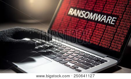 Male Hacker Hand On Laptop Computer Keyboard With Red Binary Screen Of Ransomware Attacking. Cyber A