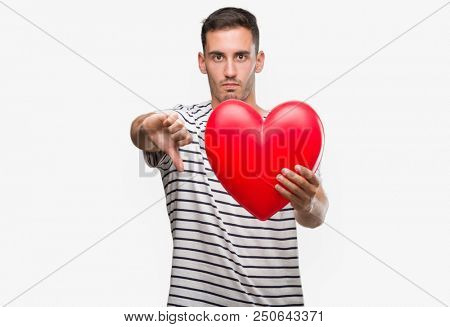 Handsome young man in love holding red heart with angry face, negative sign showing dislike with thumbs down, rejection concept poster