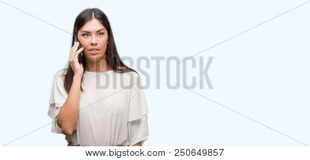 Young beautiful hispanic using smartphone with a confident expression on smart face thinking serious