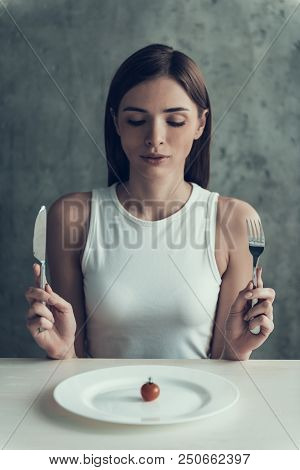 Woman Sitting On Chair And Eating Tomato On Plate. Diet Concept. Weight Loss Problem. Starving Young