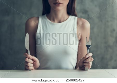 Close Up. Young Woman Sitting With Knife And Fork. Diet Concept. Weight Loss Problem. Starving Young