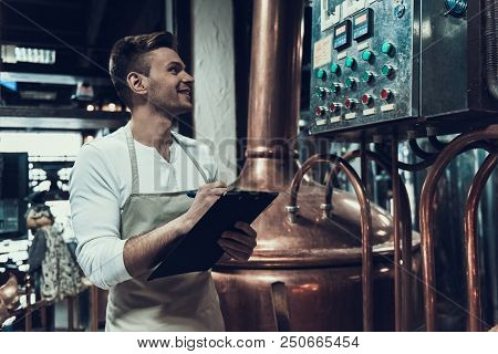 Brewer Standing Near Apparatus In Modern Brewery. Professional Brewer. Fermenting Beer. Metal Tank.