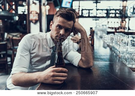 Sad Young Man with Bottle of Beer Sitting in Bar. Drunken Guy in Modern Pub. Unhealthy Lifestyle. Addicted Men. Sitting Alone. Depressed Guy with Bottle. Drunkard in Bar. Addicted by Alcohol. poster