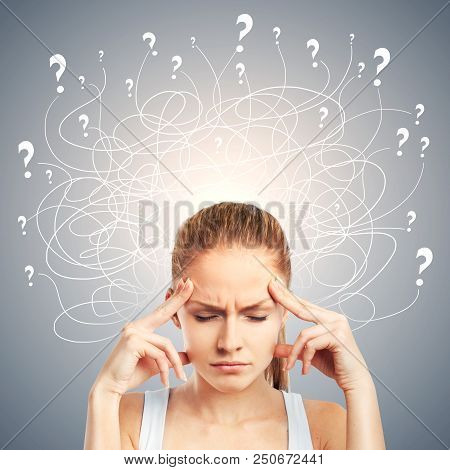 Portrait Of Confused Young European Woman On Gray Background. Confusion And Pensive Concept