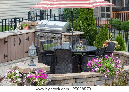 Outdoor Kitchen On A Brick Exterior Patio With Wicker Dining Chairs Under An Umbrella And Colorful S