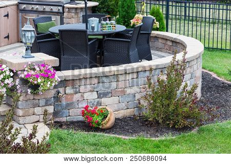 Comfortable Seating On A Raised Exterior Patio With Curved Round Brick Wall Set In A Neat Manicured