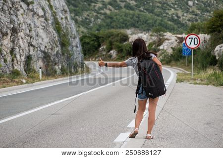 Young Backpacking Adventurous Woman Hitchhiking On The Road. Traveling Backpacks Volume, Packing Ess